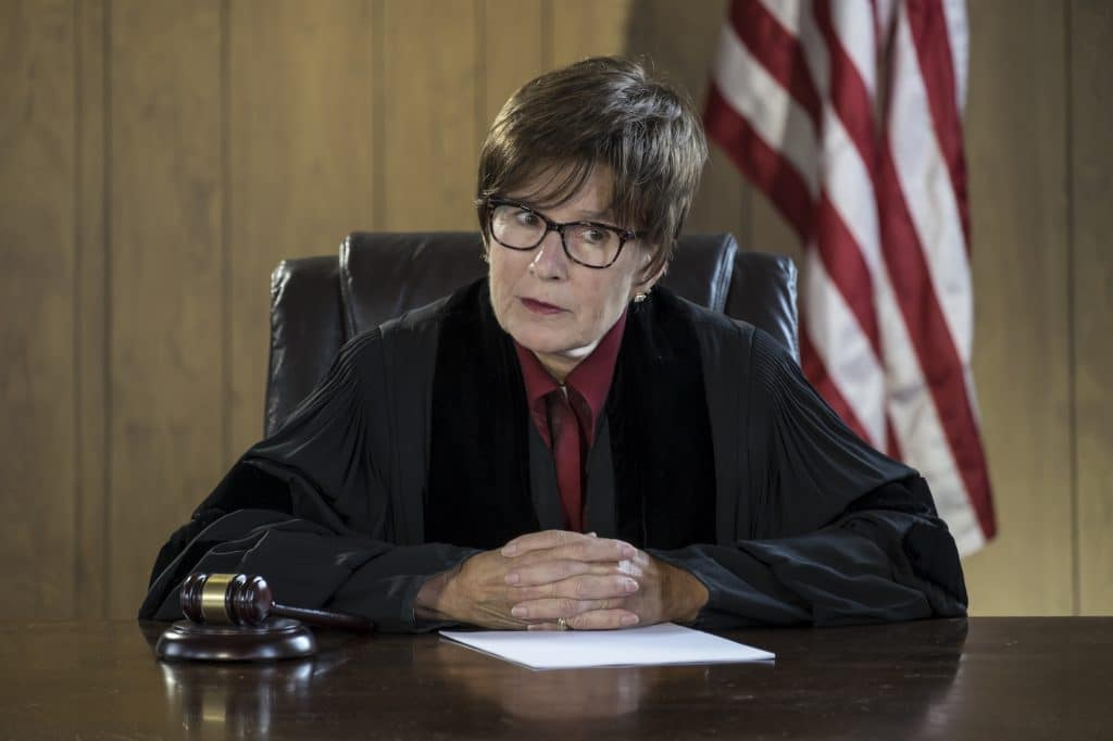 stafford-firm-can-i-go-to-jail-female-judge-gavel-american-flag-courthouse