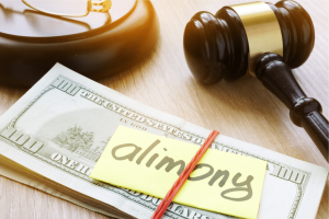 """A gavel placed beside money that's labeled """"alimony"""""""