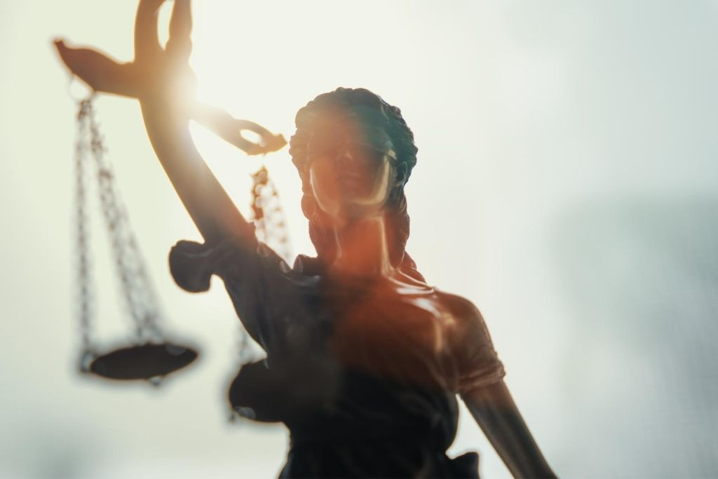 Lady Justice figure with a bright sky