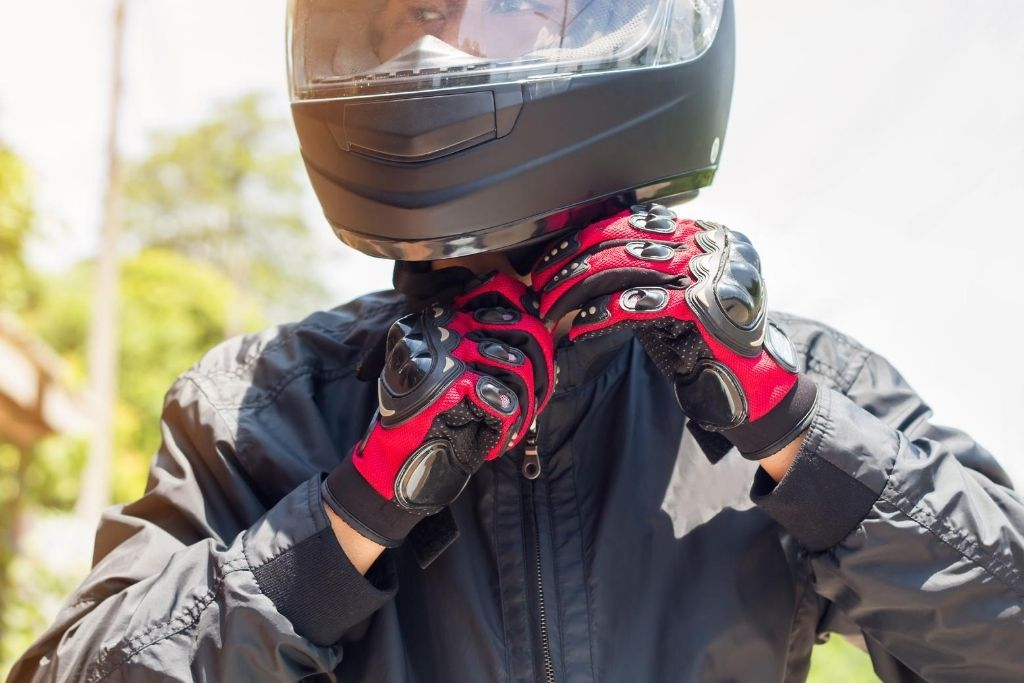 Motorcycle rider with helmet and gloves on.
