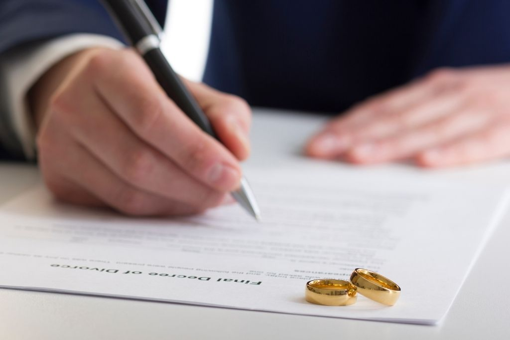 Man signing documents with two wedding rings.