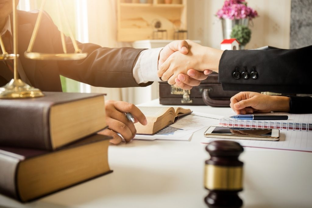A man and a woman shaking hands in a lawyer's office with a gavel and books on the table.