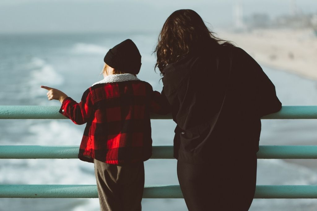 A mother and child looking at the ocean.