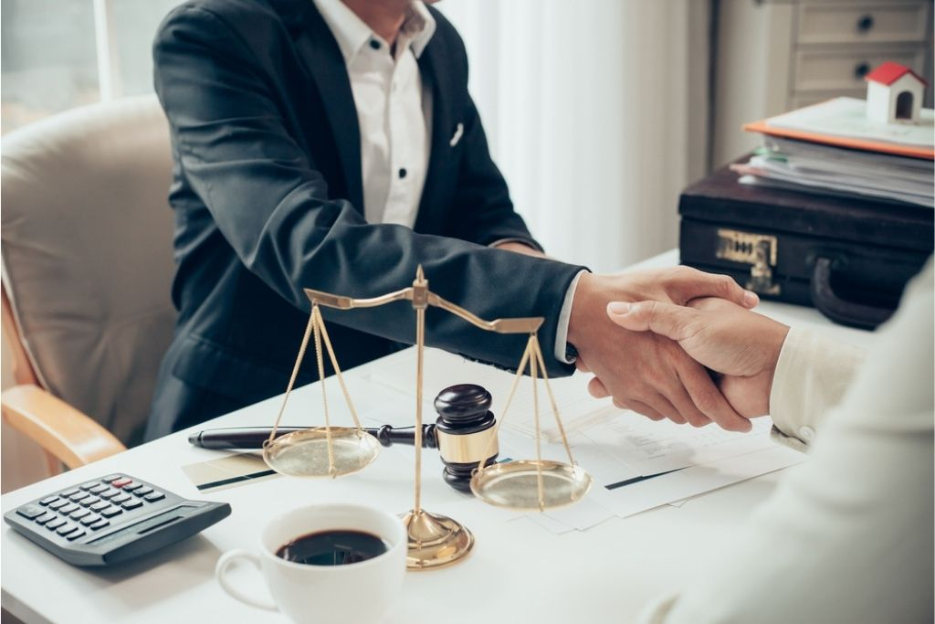 Two people shaking hands in front of an attorney's desk.
