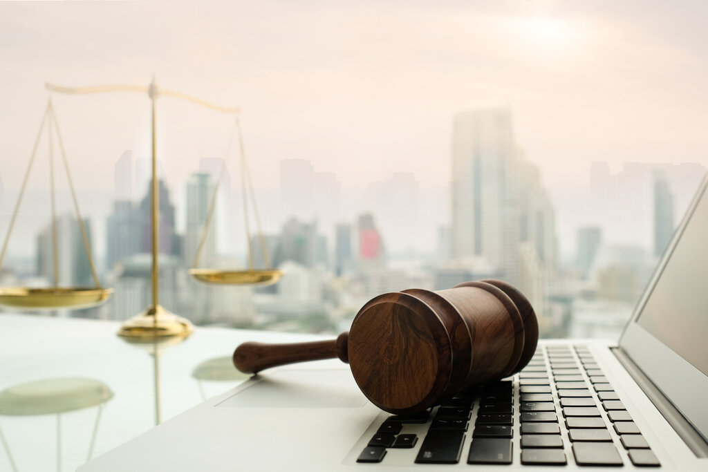 Laptop and gavel in front of a window of a large city.