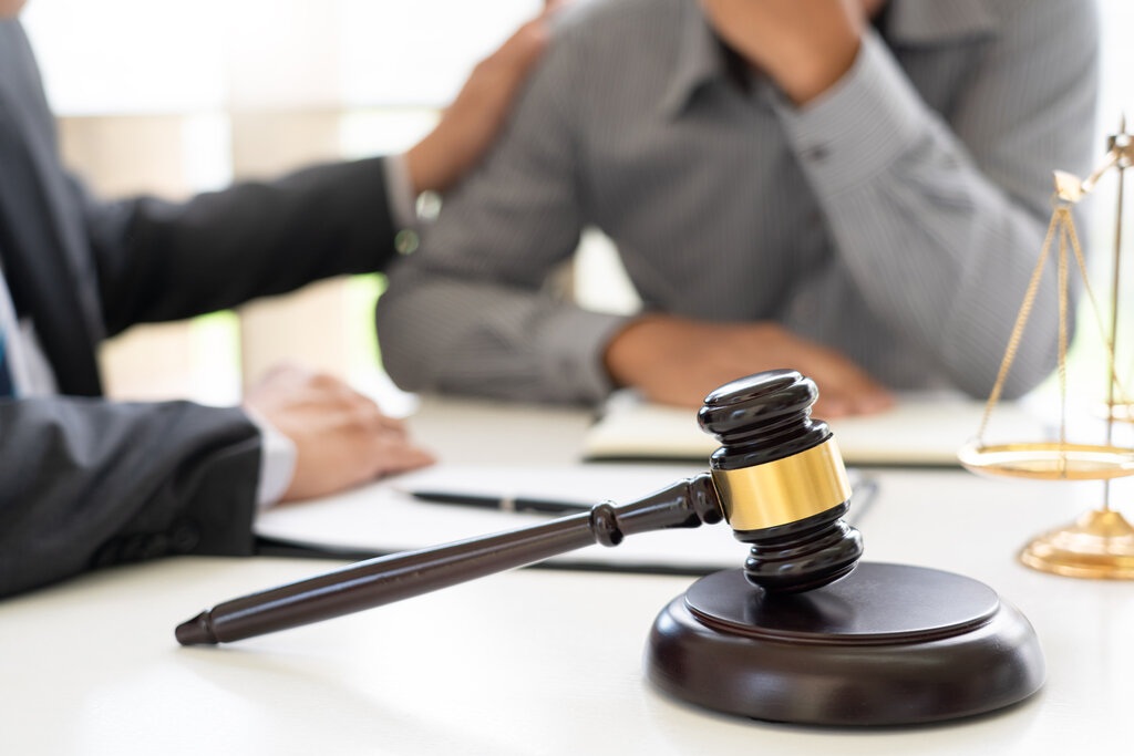 Lawyer comforting a client with a desk with a gavel on it in front of them.